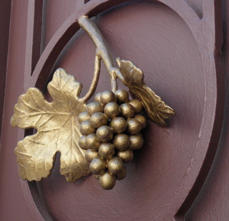 Grape leaf and bunch of grapes gilded on a church door in Israel